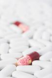 Two red pills in many white pills. Two red capsules among many white tablets. Shallow depth of field Royalty Free Stock Photos