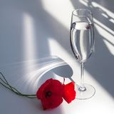 Two red poppy flowers on white table with contrast sun light and shadows and wine glass with water closeup. Two red poppy flowers on white table with contrast stock photo