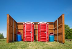 Two red portable restrooms in a park Stock Photos