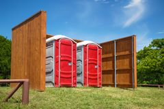 Two red portable restrooms in a park Royalty Free Stock Photography