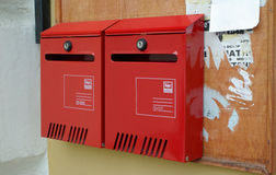 Two red postbox on the wall. Two new metal red postbox on the dirty wall and messageboard Royalty Free Stock Photography