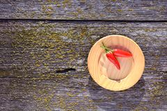 Two red  hot chili peppers in wooden plate on old  background Royalty Free Stock Photos