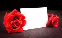 Two red roses and blank gift card for text on old wood background Stock Photography