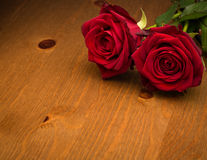 Two Red Roses On Brown Wood Royalty Free Stock Photo