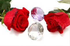 Two red roses and jewelry stones Stock Image