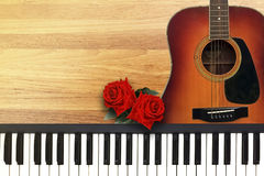 Two Red Roses with Romantic Valentine Love Song. Two Red Roses with Romantic Valentine Love Song by Guitar and piano on wooden Background Royalty Free Stock Photography