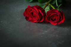 Two red roses on slate tile Stock Photo