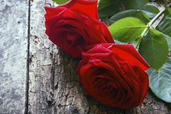 Two red roses on a wooden Royalty Free Stock Image