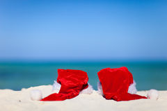 Two red Santa hats on beach Stock Images