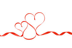 Two red satin ribbon hearts, isolated stock image
