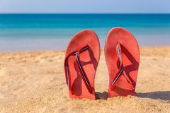 Two red slippers upright in sand of beach Stock Photo