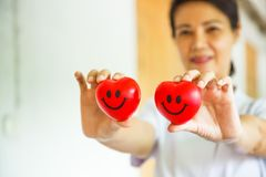 Two Red Smiling Hearts held by smiling female nurse`s hands, representing giving effort high quality service mind to patient. Royalty Free Stock Photo