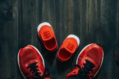 Two red sport running shoes or sneakers of mother or father and. Child on wooden background,use for father`s day or mother`s day or family`s day with sport Royalty Free Stock Photos