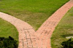 Two paths into one. Two red stone paths converges into one amid the grass and plants in Presidio park Royalty Free Stock Image