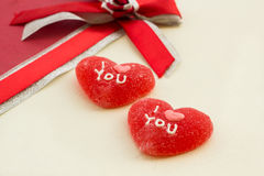 Two red sweet hearts on a gift box Stock Photos