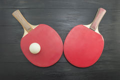 Two red table tennis paddles on dark background Royalty Free Stock Photo