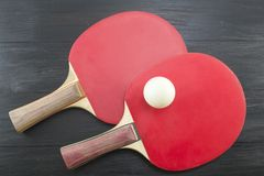 Two red table tennis paddles on dark background Stock Photos