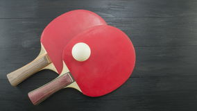 Two red table tennis rackets on dark background with copyspace Stock Photography