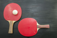 Two red table tennis rackets on dark background Royalty Free Stock Images