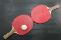 Two red table tennis rackets on dark background Royalty Free Stock Photo