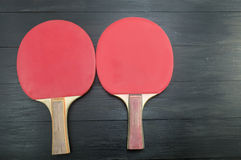 Two red table tennis rackets on dark background Stock Images