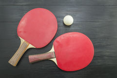 Two red table tennis rackets on dark background Royalty Free Stock Photography