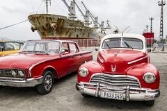 Red american classic cars and rusty ship, Santiago de Cuba Stock Image