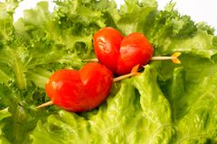 Two red tomato cherry on the green iceberg salad and lemon slidce stock image