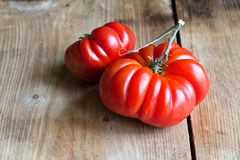 Two red tomato on wooden background Stock Image