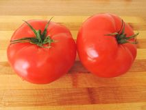 Two red tomatoes on a cutting Board. Two red ripe tomatoes on a wooden cutting Board Royalty Free Stock Photos