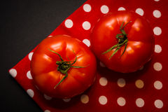 Two red tomatoes lying on the red tea-towel and black background Stock Photo
