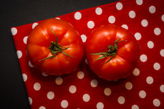 Two red tomatoes lying on the red tea-towel and black background Royalty Free Stock Photos