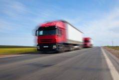 Two red trucks blurred motion Royalty Free Stock Image