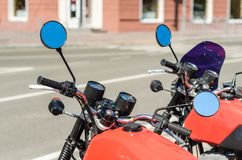 Two red vintage motorcycle cafe racer on a city street. Close up stock photos