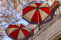 Two Red, White, and Blue Umbrellas. Two large red, white, and blue trimmed umbrellas on a terraced building stock photos