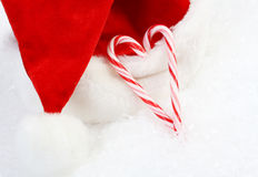 Two red and white candy canes in heart shape and Santa Claus hat on snow Stock Photography