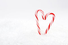 Two red and white candy canes in heart shape on snow Royalty Free Stock Photography