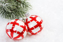 Two red and white christmas balls on snow and icing pine branch Royalty Free Stock Image
