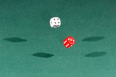 Two red and white dices falling on a green table stock photo