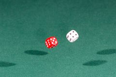 Two red and white dices falling on a green table royalty free stock image