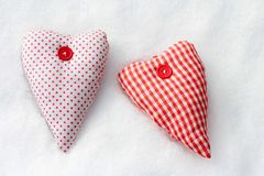 Two red-white fabric hearts in the snow.  Stock Photo