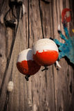 Two red and white fishing markers, buoys, hang to dry Stock Images