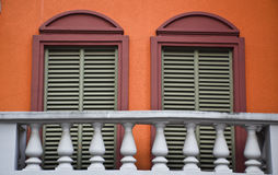 Two red Windows on the balcony. This is the construction details on a house Stock Photos