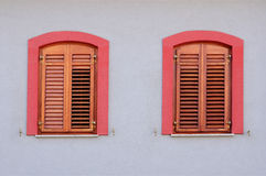 Two red windows with wooden jalousie on white wall Royalty Free Stock Photo
