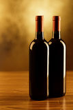 Two red wine bottles on wooden table and golden background Stock Photos
