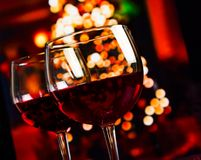Two red wine glass against christmas lights decoration background Royalty Free Stock Image