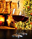 Two red wine glasses against christmas tree background Royalty Free Stock Images