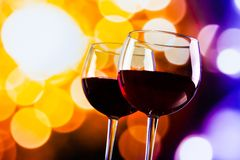 Two red wine glasses against colorful bokeh lights background