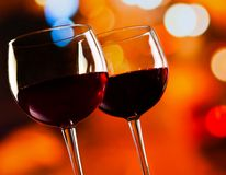Two red wine glasses against colorful bokeh lights background Royalty Free Stock Image