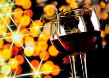 Two red wine glasses against golden bokeh lights background Royalty Free Stock Photography
